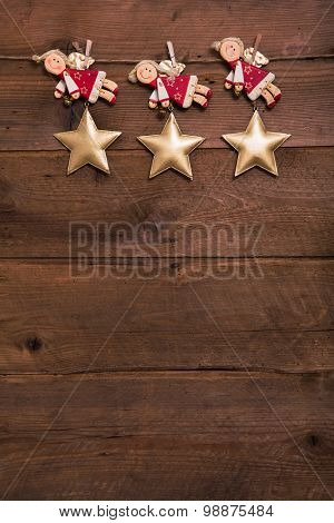 Three red and golden Christmas angels on old wooden background for a greeting card.