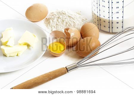 Baking Ingredients For Pancakes, Butter, Eggs, Flour, Milk And A Whisk