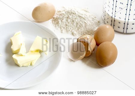 Baking Ingredients, Butter, Eggs, Flour And Milk On A White Background