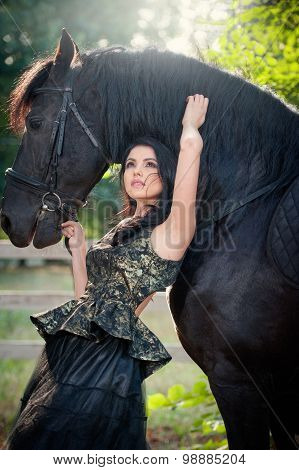 Fashionable lady with black royal dress near brown horse. Beautiful young woman