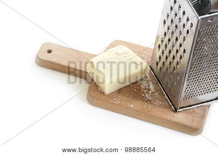 Parmesan Cheese And  Metal Grater On A Kitchen Board
