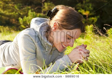 Pretty Young Woman Lying In Green Gras, laughing