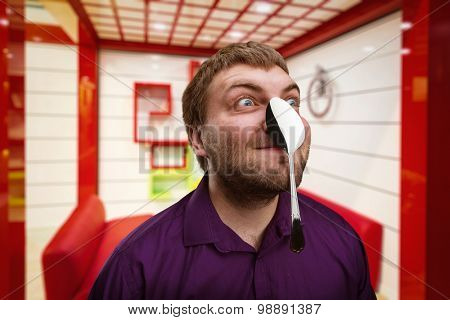 Adult man holds a spoon on his nose