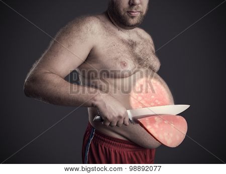 Man cuts a slice of sausage from his belly
