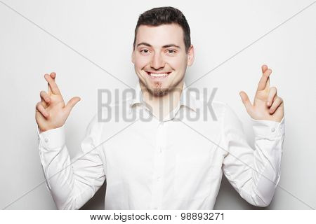 life style, business  and people concept: business man in shirt keeping fingers crossed  while standing against white background