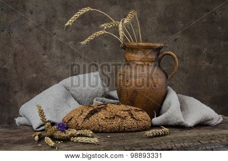 Baked Bread, Crock And Spikelets On Wooden Boards