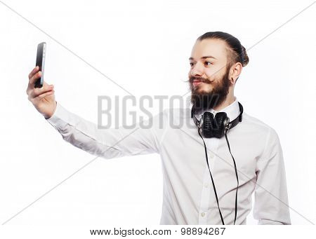 Internet, tehnology and people concept: a young man with a beard in shirt holding mobile phone and making photo of himself while standing against white  background.