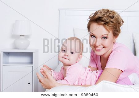 Beautiful Mother Lying With Her Baby On The Bed