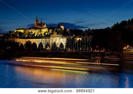 Prague Castle In Hradcany With Vlatava River And Lights From Boats