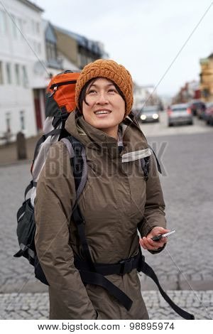 beautiful Asian tourist walking in city looking around smiling wearing beanie and rain jacket