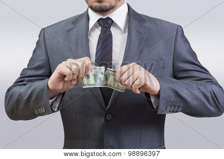 Businessman tearing up dollar bill