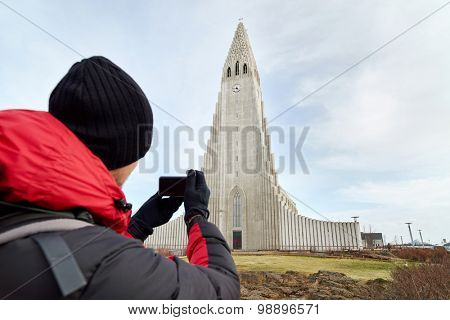 rear view adventure travel backpack man taking pictures of the Hallgrimskirkja cathedral in reykjavik iceland