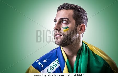 Brazilian fan holding the Brazilian flag on green background