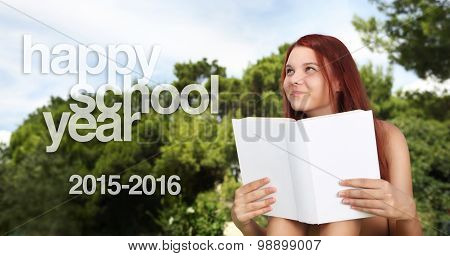 school girl at the park with the book and written happy school year 2015 2016