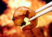 stock photo of flame-grilled  - king tiger prawn shrimp with chop sticks by bbq fire macro close up copy space - JPG