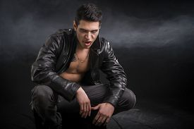stock photo of jacket  - Portrait Of An Angry Wounded Young Male Vampire in Black Leather Jacket - JPG