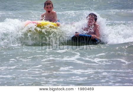 Two Boys Playing In Ocean