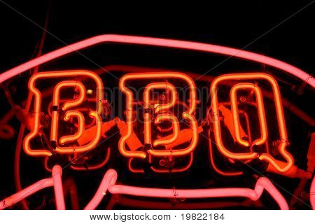 Red neon sign of the word 'BBQ' inside the outline of a pig, on a black background.