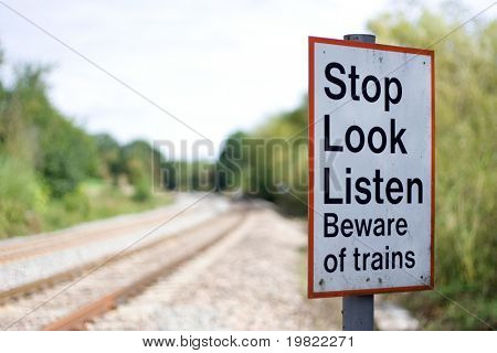 Warning sign next to a high speed railway line advising pedestrians to Stop, Look and Listen before crossing the tracks.