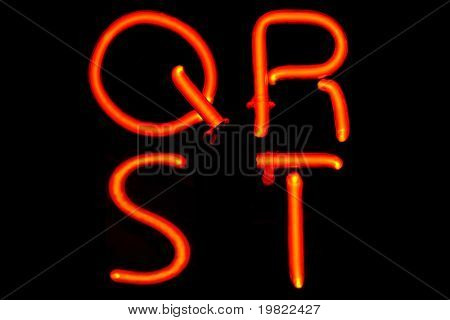 Red neon letters of four letters of the alphabet (QRST).