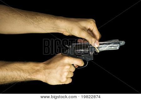 Male hand putting a condom in a revolver. Black background.