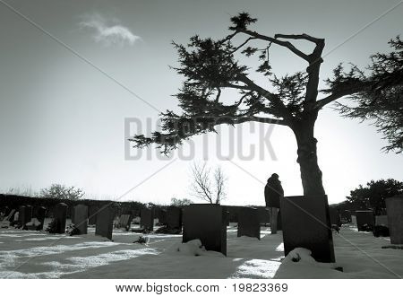 Lonely figure standing amongst tombstones in snowy cemetery.