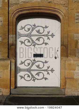 White door with ornate metalwork hinges with floral design