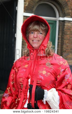 ROCHESTER CITY, KENT ,ENGLAND - DEC 11:Woman in red  dress plays part of Dickens character at Dickens Festival in Rochester December 11, 2010. Dickens Festival is an annual literary event.