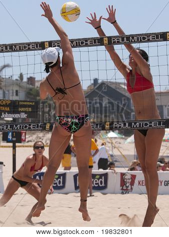 MANHATTAN BEACH, CA. - JULY 18: Barbra Fontana spikes the ball and Mariko Coverdale attempts to block at the AVP Manhattan Beach Open July 18th 2009