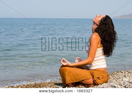 Young Woman Meditation In The Beach