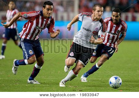 CARSON, CA. - AUGUST 22: Chad Barrett (MID) dribbling away from Maykel Galindo (R) & Jesus Padilla (L) during the Chivas USA vs. Toronto FC match on August 22, 2009 at the Home Depot Center in Carson.