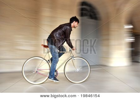 Young man riding a fixed-gear bicycle