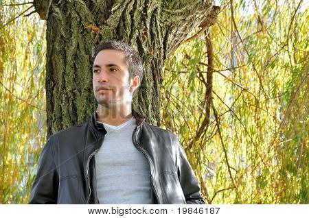 Young man leaning against a willow tree