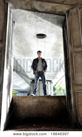 Young man standing under a bridge