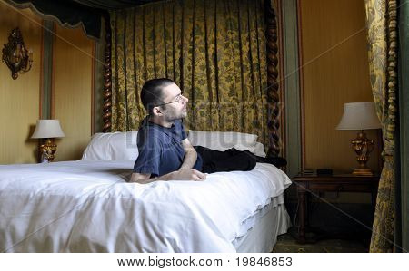 Young man leaning on a canopy bed