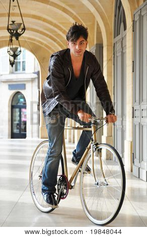 Young man riding a fixed-gear bicycle also called fixie
