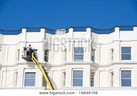 Man cleaning windows of a beautiful english building