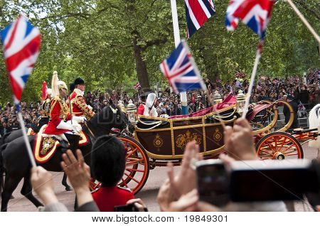 LONDON, UK - APRIL 29: Prince William and Kate Middleton in their carriage on their way to Buckingham Palace after the wedding, April 29, 2011 in London, United Kingdom
