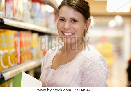Close-up of a shopper in shopping centre smiling and looking at camera