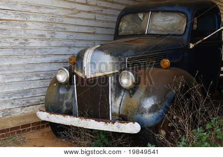 A rusted old pick-up truck parked in a weed-choked carport