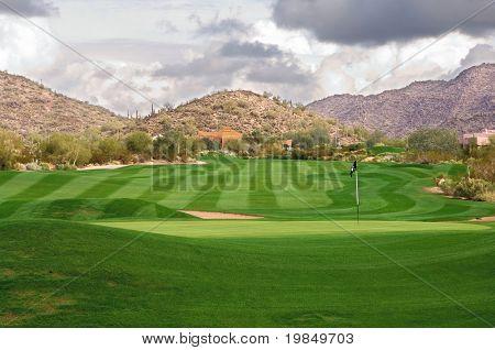 Um exuberante, manicured Arizona golfe com nuvens sobre montanhas