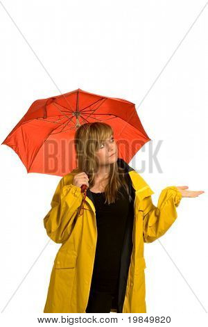 A pretty young woman in a raincoat and holding an umbrella checks to see if it is raining (isolated against white background)