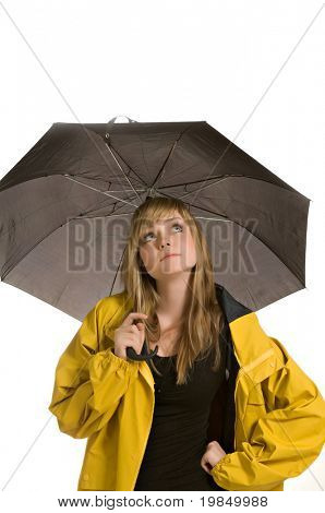 A pretty young woman, isolated against a white background, wears a yellow raincoat and holds a black umbrella, waiting for rain