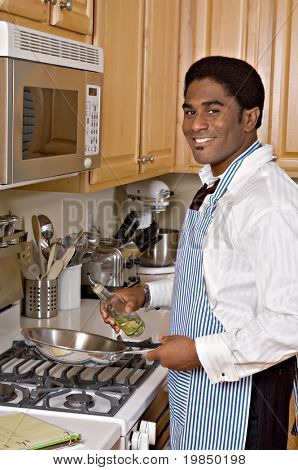 Handsome African-American businessman cooks dinner after work