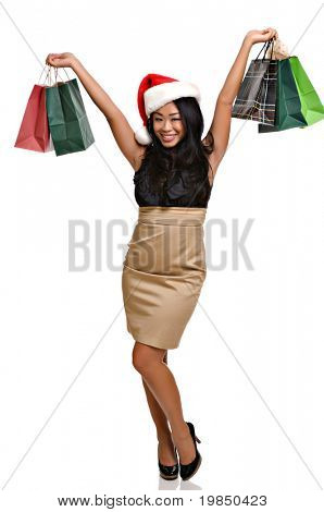 Beautiful Asian woman holds Christmas shopping bags after a successful raid on the mall