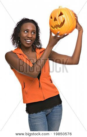 Happy young African-American woman holding jack-o-lantern