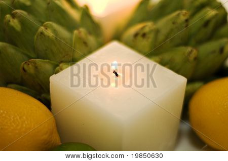 Shallow focus image of contemporary centerpiece with candles, artichokes, lemons, limes