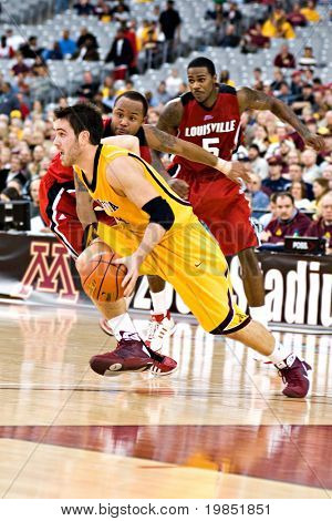 GLENDALE, AZ - DECEMBER 20: Minnesota's Travis Busch #4 dribbles past Louisville's Jerry Smith #34 and Earl Clark #5 on December 20, 2008 in Glendale, Arizona.
