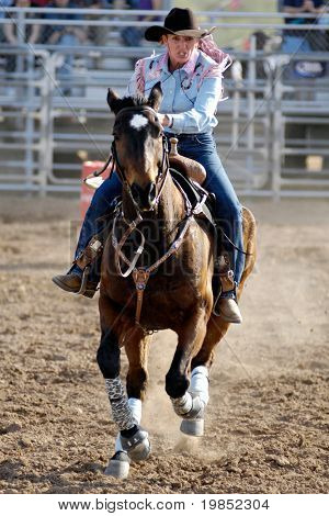 APACHE JUNCTION, AZ - FEBRUARY 28: A female competitor rides a horse in the barrel race competition at the Lost Dutchman Days Rodeo on February 28, 2009 in Apache Junction, AZ.
