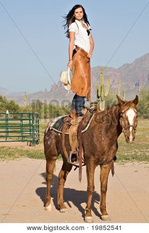 A young woman stands in the saddle on the back of her horse